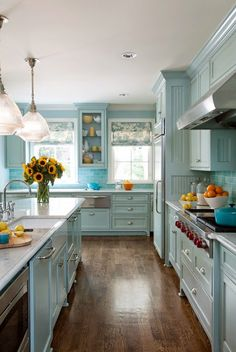 The walls and kitchen cabinets are painted Tidewater by Sherwin-Williams. Tobi Fairley Interior Design