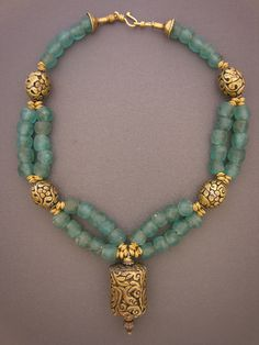 Aquamarine recycled bottle glass beads from Ghana play host to four repousee beads and a cylindrical pendant from the Nepal/Tibet region.
