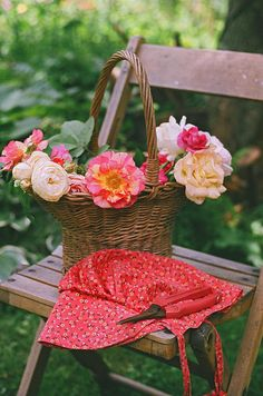 Pretty moments from a garden: A chair, red hat, and a basket filled with roses.