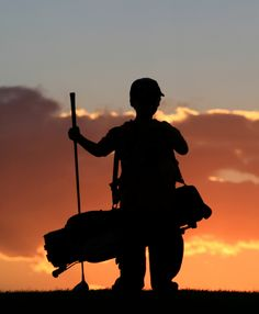 Photo of child silhouette with driver & golf club bag at sunset.