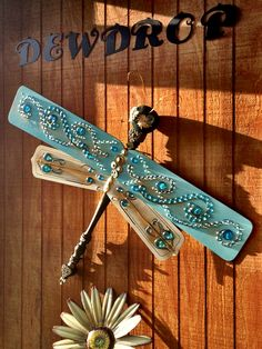 Dragonfly-- An idea I found on Pinterest. I decorated mine with misc old jewelry and glass beads.  You will need ceiling fan blades and a spindle (or table leg) for the body. Attach with screws. Head could be wooden ball or styrofoam.(inspiration only)