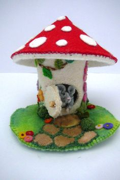A little grey mouse peers form the open door of a mushroom house.