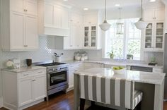 white kitchen with gray and white tent-stripe upholstered double bar bench. #DeltaFaucetInspired