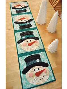 "The smiling faces on these snowmen will make the wintry days a little brighter and much more cheerful! Finished size is 12 1/2"" x 53""."