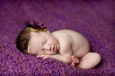 Baby laying on purple blanket