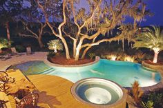 This freeform infinity pool and spillover spa was designed and built around the existing landscape and oak trees. The entire scene is breathtaking at night. Aquatech Pools by John Clarkson, Jacksonville, Florida http://www.luxurypools.com/builders-designers/aquatech-society.aspx