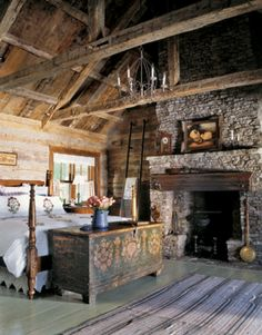 Fireplace--Country Living  Vintage and antique flea market finds and heirlooms decorate this stone and wood filled rustic cabin bedroom.  Love the painted chest at the foot of the bed that adds color to the room.