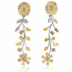 A flower motif prevails in this pair of 18K three-toned gold earrings featuring a spectacle of natural fancy colored diamonds. A pair of oval cut Fancy Vivid Yellow diamonds are surrounded by halos of 36 pave-set round Fancy Yellow diamonds and encircled by a petal-like frame of larger fancy multicolored multishaped diamonds, are the anchors of the earrings. Fancy multicolored diamonds of varying shapes, serving as leaves, decorate a winding stem, at the base of which sits a six-petaled ...