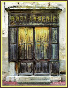 Aged facade of a very old bakery shop. not in use any more. Blaye, France.