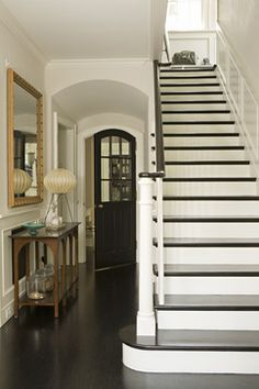 I am officially obsessed with black wood work.  The black door, stairs and handrail are so elegant.