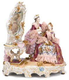 Dresden porcelain figural group of ladies dressing:  circa 1900, Depicting two maidens in floral patterned gowns with lace with a rococo style dressing mirror and table
