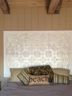 using tin tiles on a framed board, all painted white. add texture to the guest room and a beautiful headboard