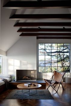 Living room, large window, beams, wooden chairs, coffee table, fireplace, rug