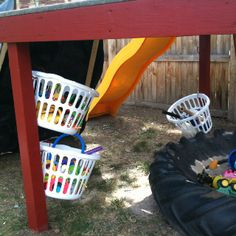 Outdoor toy storage under a play set using laundry baskets and large hooks.