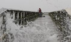 Waves crash against the shore as Chino Crawley and Rufus Adkinson brave afternoon storms to fish from Hilton Pier on Monday. (Photo by Kaitlin McKeown / Daily Press)