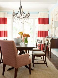 A feel-good blue keeps dining room walls fresh and bright, while a traditional dining set is shaken up with vivid touches of color. Stationary curtain panels were stitched from horizontal strips of coral and white linen. Dark wood tones found in the table and chairs ground the light hues.