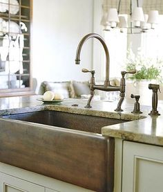 Copper Apron-Front Sink  Farmhouse sinks are manufactured in a wide range of materials: cast iron, stone, or metal. Here, a copper apron-front sink with vintage bridge style copper faucets adds retro style to this modern kitchen --