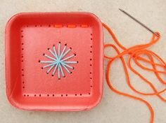 Embroidery on recycled Styrofoam trays, poke holes first with needle, then use yarn to fill in.