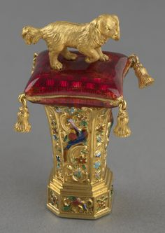 Seal surmounted by a gilt bronze spaniel standing on a guilloché enamel tassled cushion. The body cast and enamelled with exotic birds, squirrels and flowers. Onyx matrix. Gilt bronze, enamel, onyx.