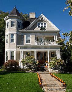 Vintage Victorian house decorated with orange pumpkins for fall.