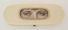 Ivory patch box with hand-painted eyes framed by a band of rose gold. Hinged box has a velvet lined interior with a mirror inset into the lid. 1790