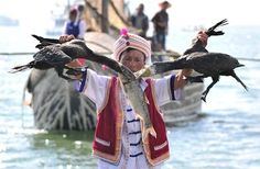 Image: A Chinese Bai ethnic minority fisherman pulls two cormorants away from a fish during Erhai lake fishing opening festival in Dali (© SHENG LI//Reuters)