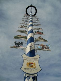 "A ""Maibaum"" is this thing. In Bavaria, it's decorated with the Bavarian colors of blue and white, and decorated with local symbols. They seem to be used like large signposts or billboards — the decorations reflect the different craftsmen or trades that the market or village provides — a butcher or cobbler or so on.  Pinned by www.mygrowingtraditions.com"