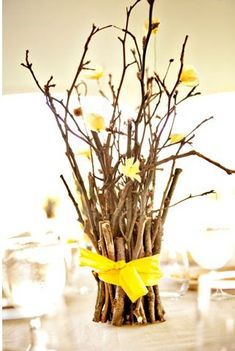 Centerpieces. Sticks wrapped in twine , with baby wild flowers. Cute and cheap. :) @ Kimbre Gibson