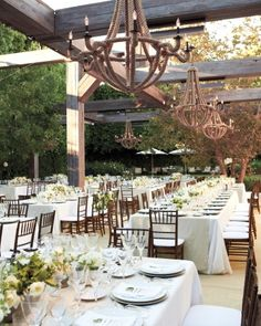 Rope-and-iron chandeliers provide illumination for this outdoor dinner