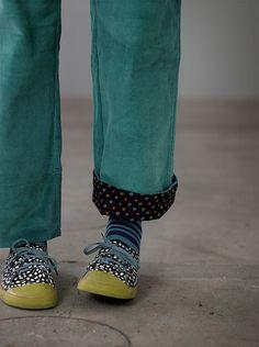 """Feincordhosen mit Elastikbund hinten, seitlicher Knöpfung und Seitentaschen. Bund und Beinabschlüsse sind mit dem Muster """"Iris"""" gefüttert, darum kann man die Hosenbeine ruhig auch mal umgekrempelt tragen."""