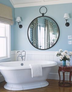 LOVE THAT MIRROR! The light blue and soft white colors are anchored by the wooden floor and side table, which makes for a soothing master bath. Over an existing bathtub, designer Michael Smith hung a new round mirror from JF Chen. Walls are painted in Pratt & Lambert's Coos Bay
