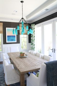 A Family Home Receives a Bold Boho Transformation//eclectic dining room, farmhouse dining table, seagrass wallpaper