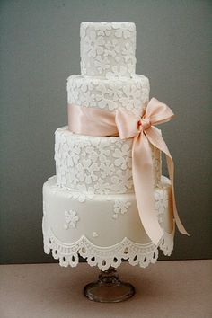 Beautiful rustic country-chic wedding cake with lace details, burlap color, and peach ribbon. #weddingcakes #rustic #country-chic
