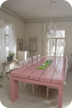 Toves Sammensurium: Pink-painted plank table in a Swedish dining room with white Swedish chairs, white beadboard walls, sheer white curtains, pale gray cornice molding, chandelier- I need this table