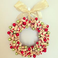 """Wine cork Christmas wreath, made using: 12 inch foam wreath, leftover wine corks, two strands of faux decorative holly, mini Christmas """"fillers"""" (found at Michael's), and a hot glue gun. Glue corks to foam wreath then decorate as desired! Don't forget to leave a space for wire or ribbon to hang!"""