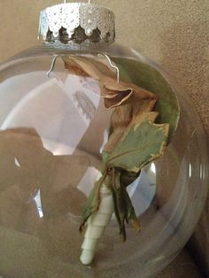 Put the boutineer in an ornament./ mom's should do this with son's prom or sport's award boutineer with date..& a small picture