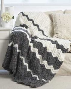 Wavy stripes gently flow from dark to light. Blanket is shown in Bernat Soft Boucle.