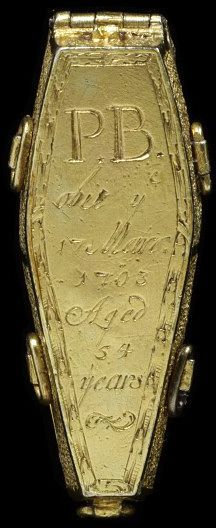 """1703 British Pendant at the Victoria and Albert Museum, London - From the curators' comments: """"This intricate jewel is in the form of a coffin which opens to reveal a panel of woven hair, initials, and an enamelled skull. It is an unflinching reminder of man's mortality while specifically commemorating the death of a particular individual, the now unknown PB. Such graphic imagery was a widely accepted part of the rituals surrounding death in the years around 1700."""""""