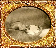 This is a beautiful postmortem photo. A little sleeping beauty with flowers placed in her hands and around her neck.