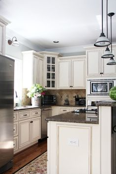 Bright kitchen with cream colored cabinet and Restoration Hardware Silver Sage paint.