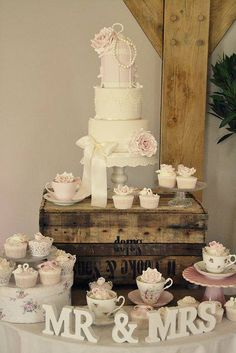 Vintage tea cups and wooden boxes for displaying the wedding cake