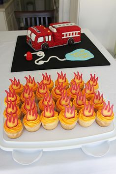 fire truck cake  The icing is yellow/orange buttercream, and the flames are made out of candy melts. I printed out a picture of a clipart flame, and traced it a bunch of times to make the candy topper for each cupcake.