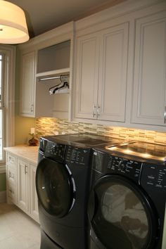 Suzie: HGTV - Nashville123 - Laundry room with light gray cabinets, black front load washer & ...