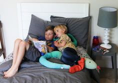 Project Nursery - Shared Boys' Room Momma's Gone City Jack and Beau of #theoandbeau read a book on their new Naturepedic kids twin mattress!