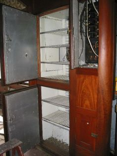 """Wine Storage"" compartment doors open alongside the electrical panel. These cabinets are located in the entry way into the old dining car."