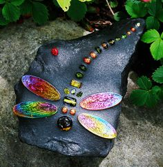 dragon flies, dragonfly art, painted stones, flower beds, rainbow colors, mother earth, mosaic, stepping stones, garden rocks