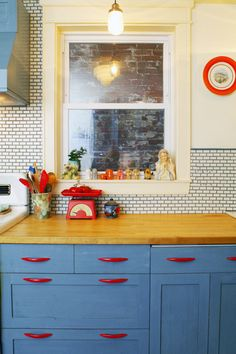 Blue stained wood cabinets and wood countertop