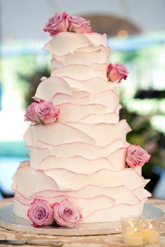 Sweet pink-tipped ruffled icing wedding cake.