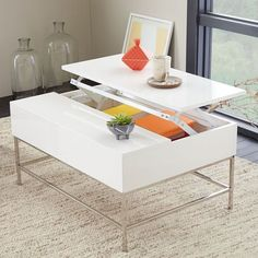 Our popular Rustic Storage Coffee Table gets a glamorous makeover in lacquered white. One side of the tabletop pops up to reveal a hidden cache of storage. Lofted on airy steel legs, there is enough room to stow anything from magazines and remotes to pillows and throws.