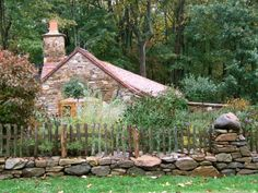 Charming cottage, love the stacked stone wall & fence...